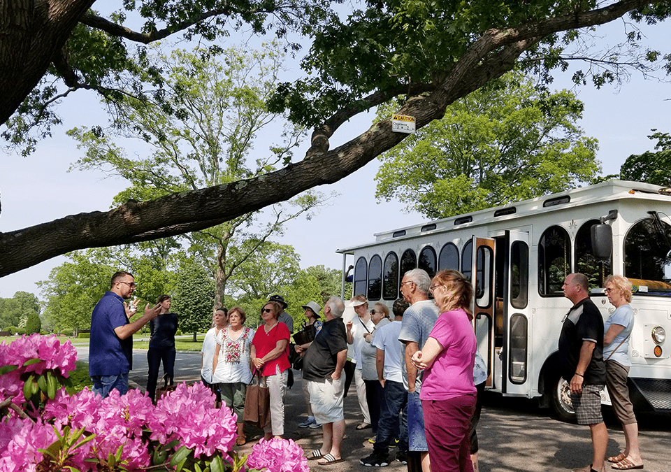 People listening to expert outside of trolly at 3rd annual arboretum tour