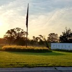 Pinelawn Memorial Park sign and flag at sunrise