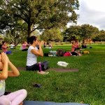 people sitting in yoga pose outside